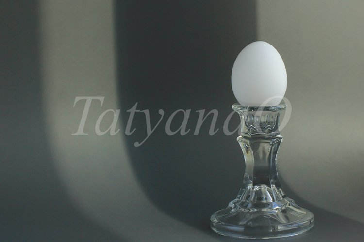 A white chicken egg in a vintage classic glass candlestick example image 1