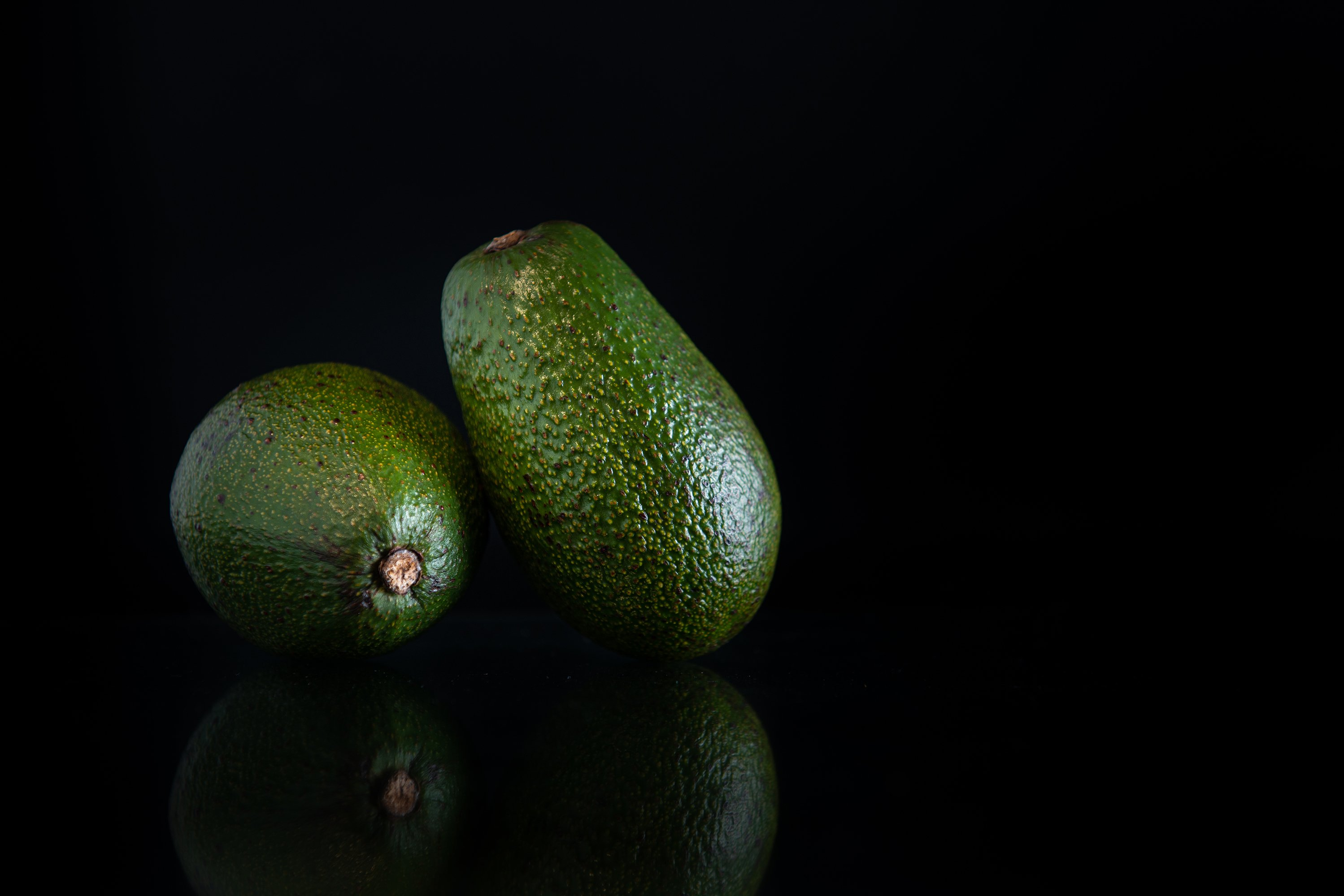 two whole avocados with reflection and copy space on a black example image 1
