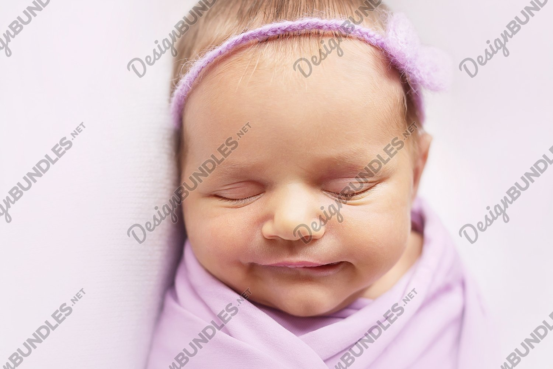 Smiley newborn baby girl is sleeping on the light pink example image 1