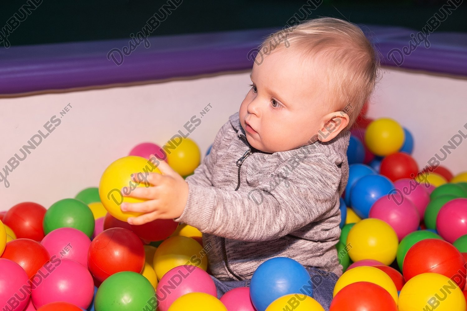 Photo of a baby boy plays with colorful balls in playground example image 1