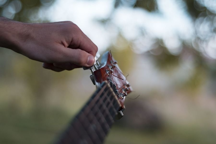 Man plays on acoustic guitar in a park example image 1