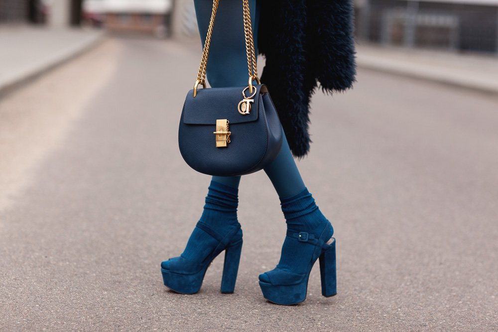 Stylish girl in a blue fur coat with a handbag in high heels example image 1