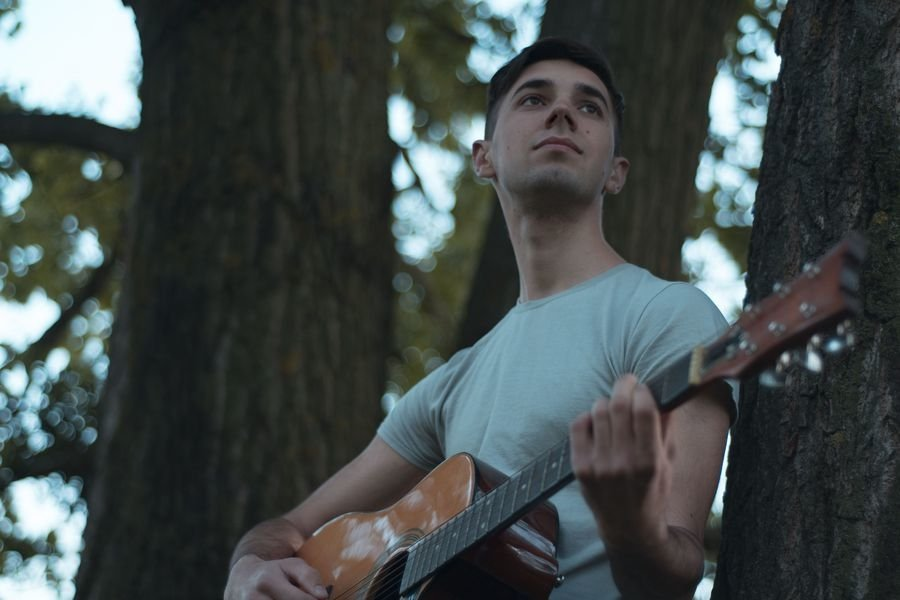 Man plays on acoustic guitar in park example image 1