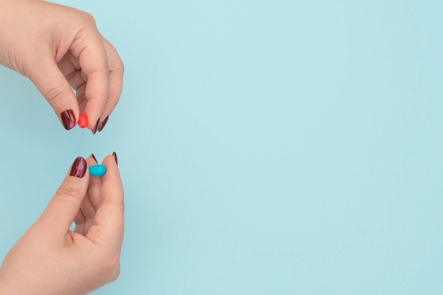 Red and blue pills on female hands on blue background example image 1