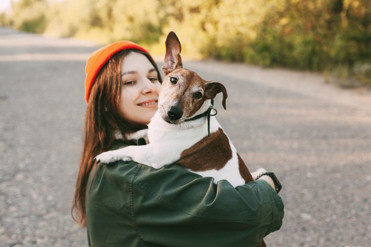 A pretty brunette holds her dog in her arms and smiles. example image 1