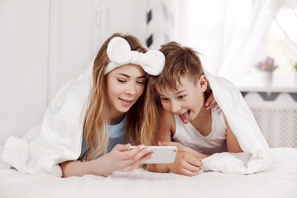 The girl and her younger brother look at photos on the phone example image 1