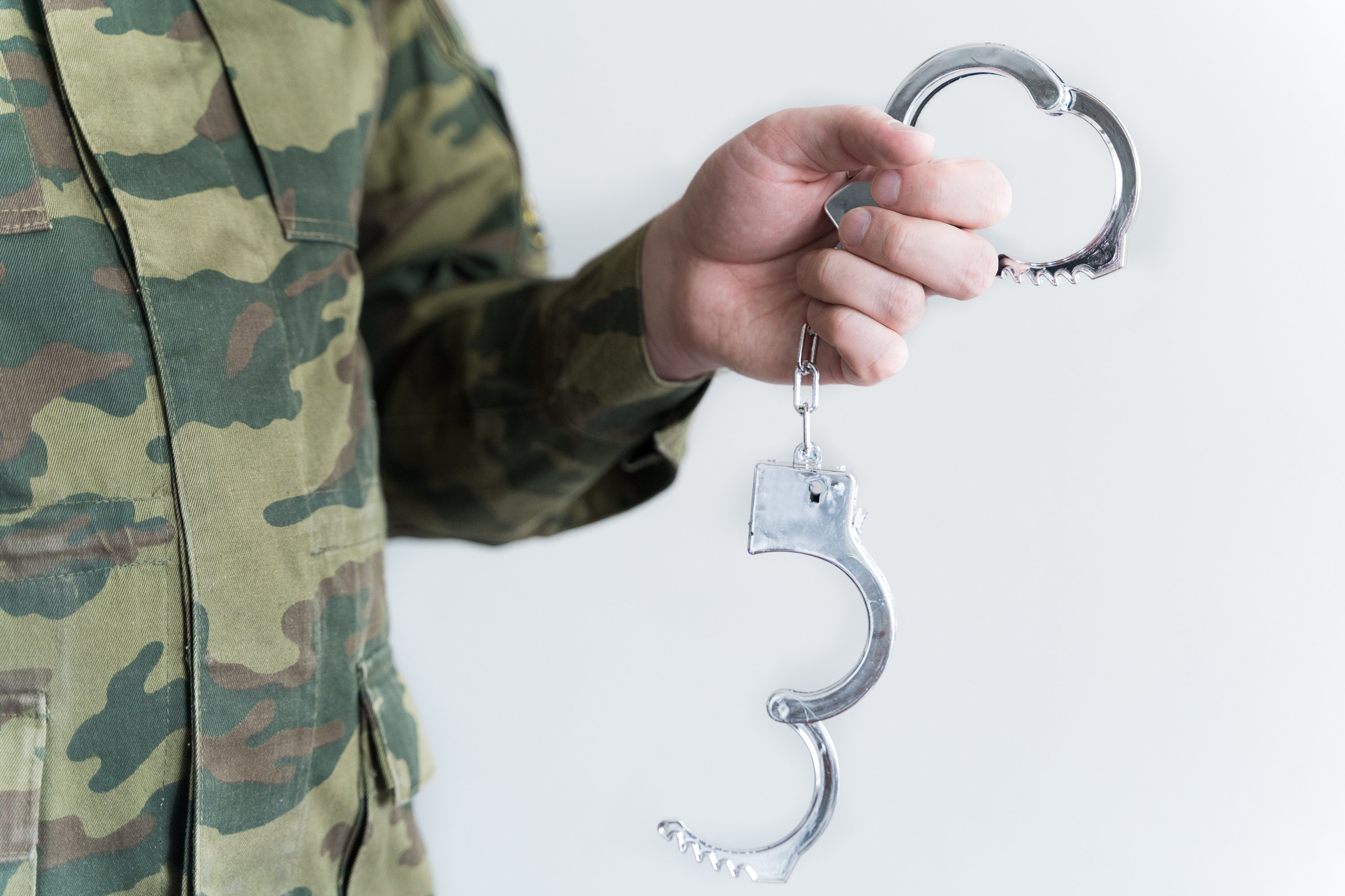Police officer with handcuffs. Self-isolation violation fine example image 1