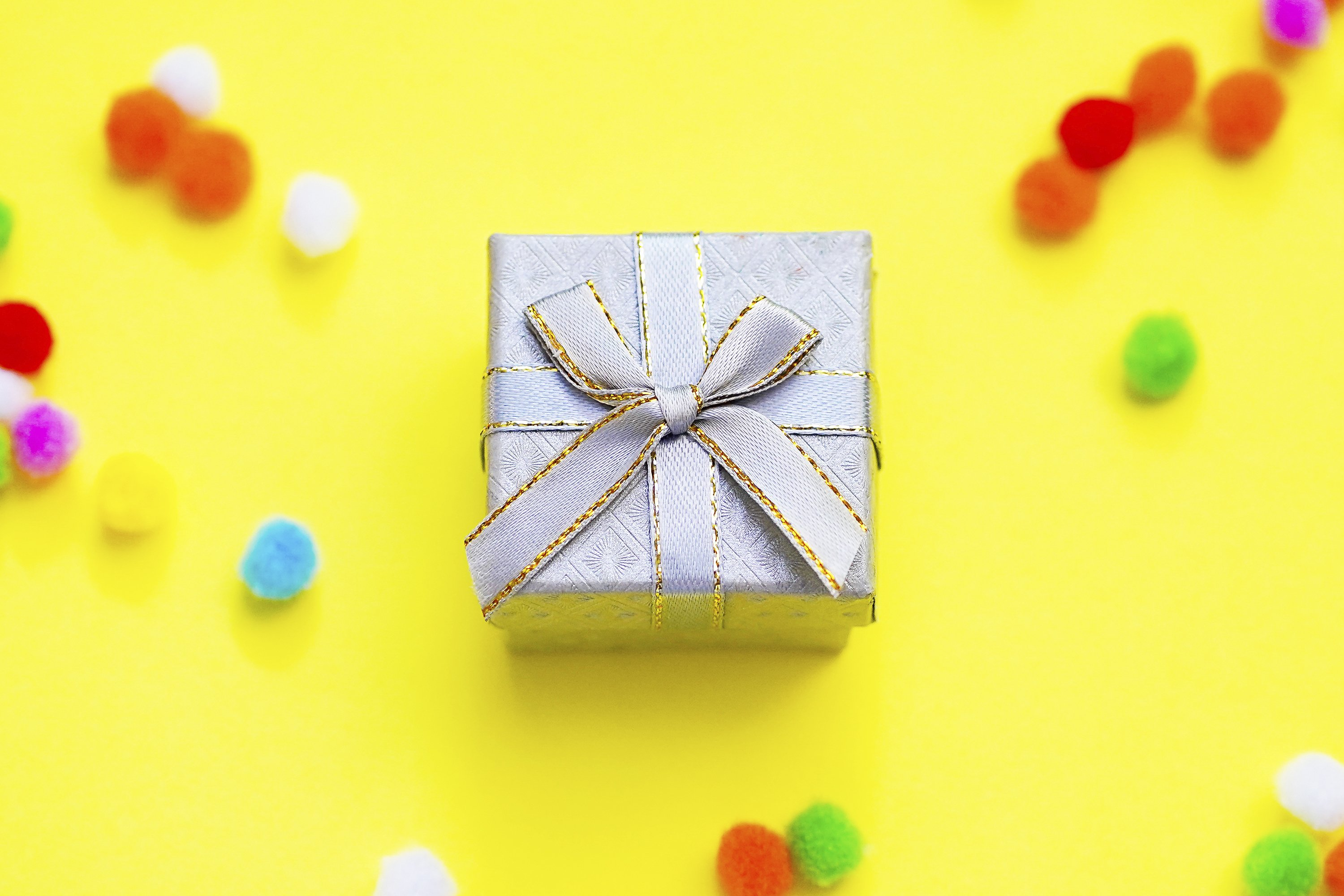 Gift box with multi-colored confetti on a yellow background example image 1