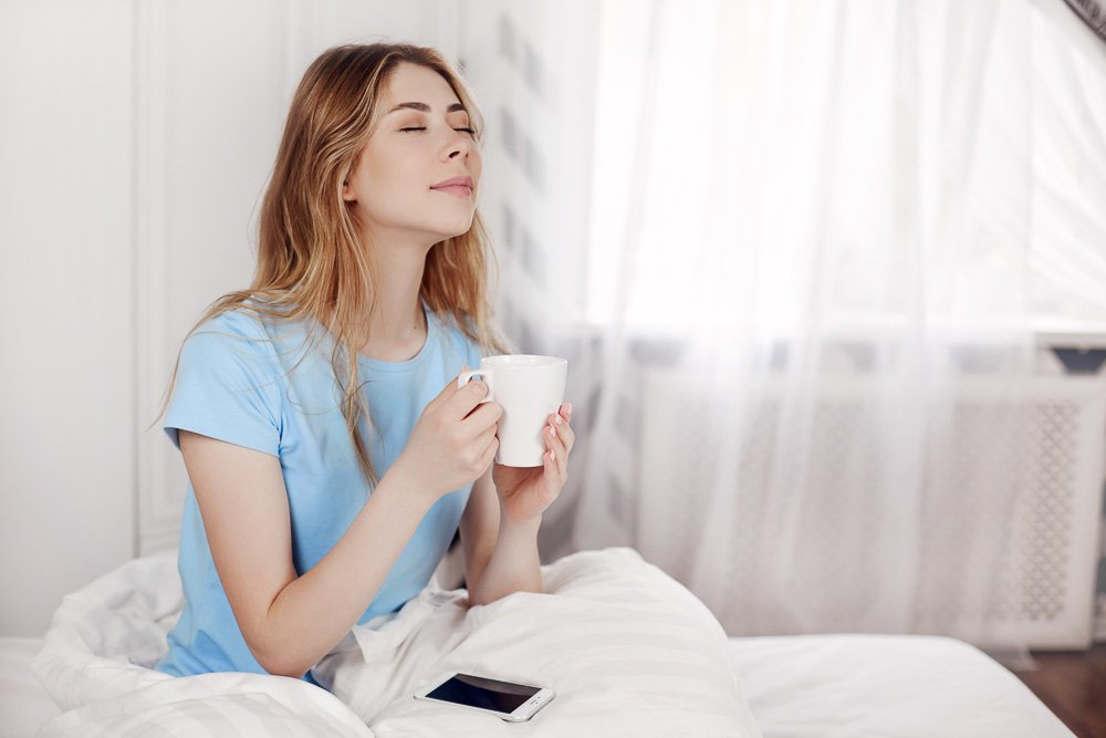 Beautiful girl drinking morning coffee sitting in bed. example image 1