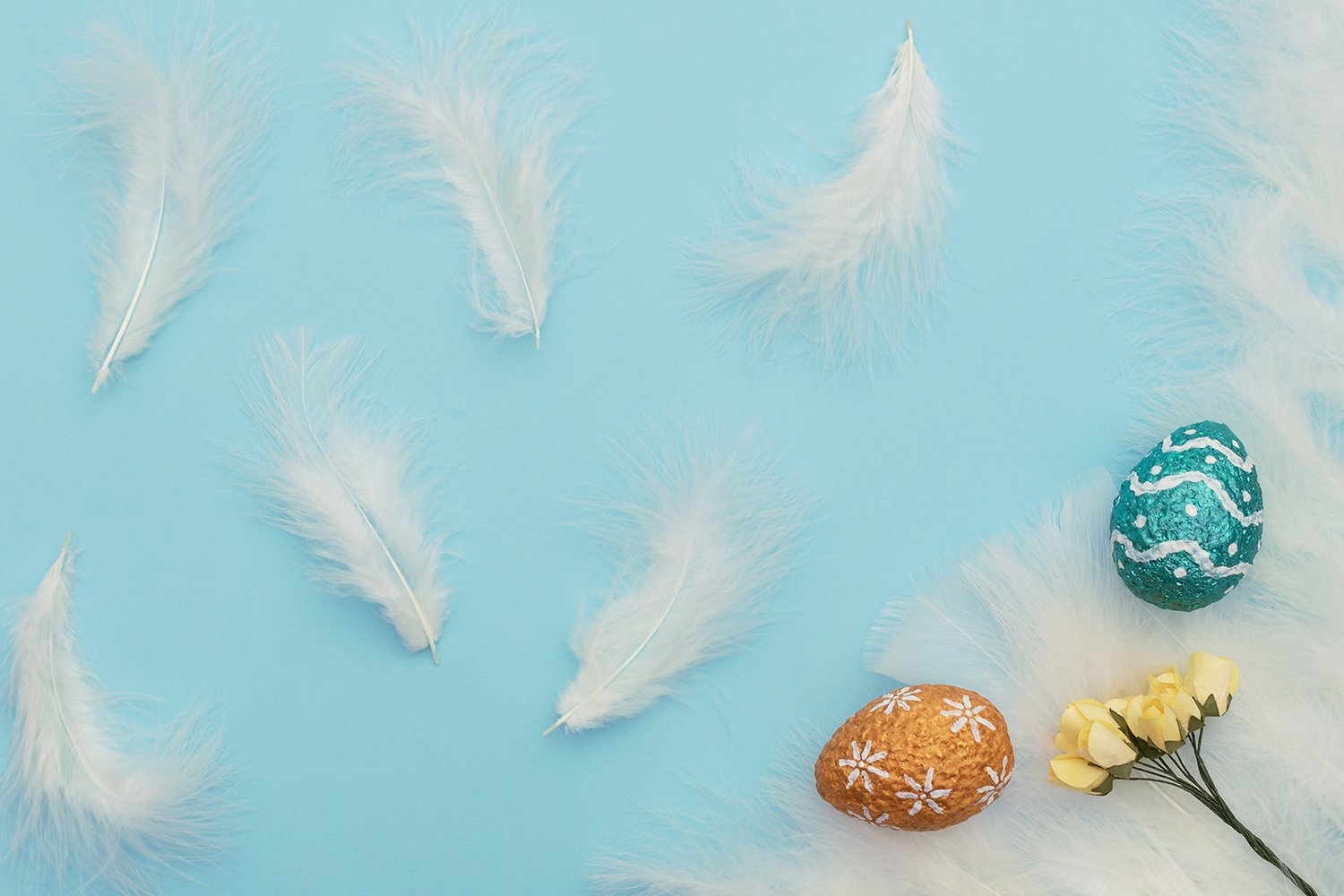 Easter eggs with yellow spring flowers and white feathers example image 1
