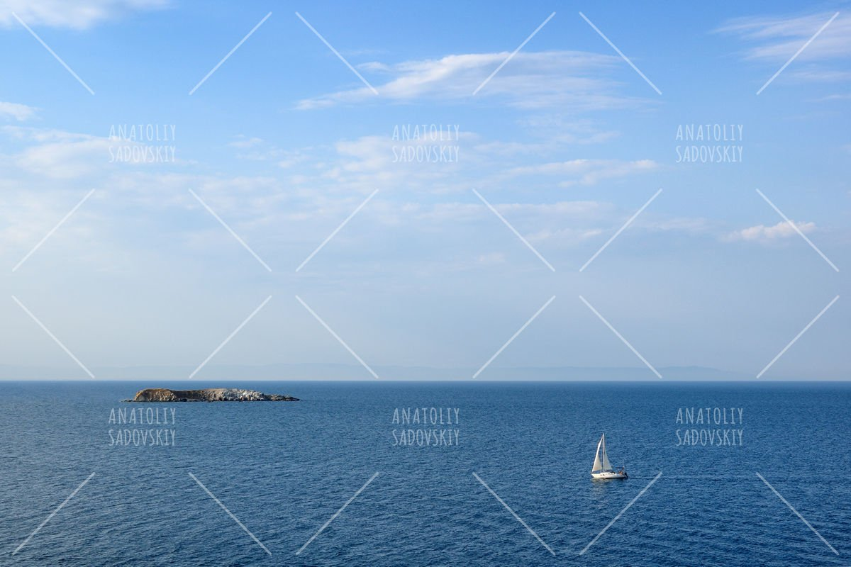 Seascape with sailing yacht and small island in sea example image 1