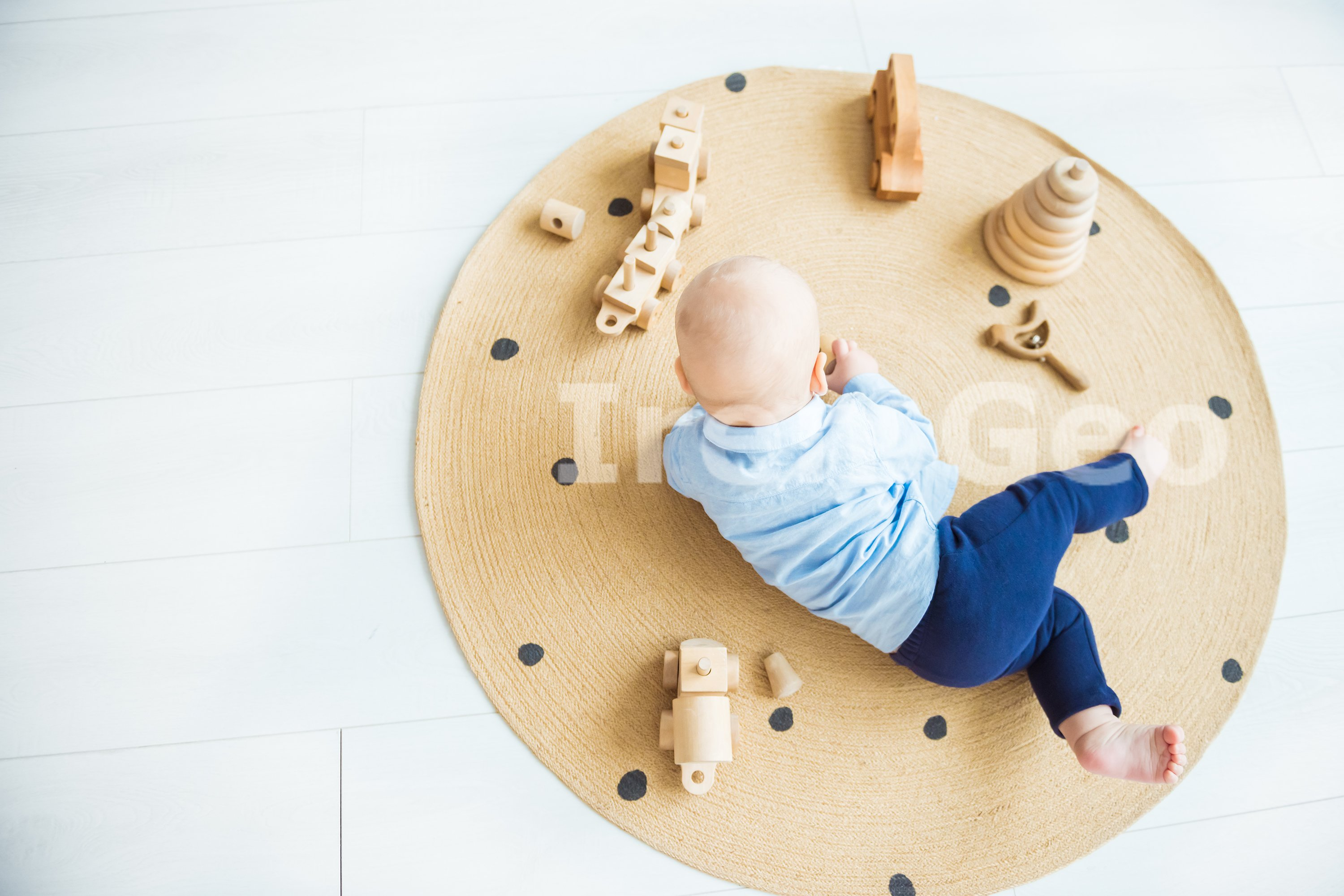Baby boy playing with wooden toys lying on the Mat example image 1