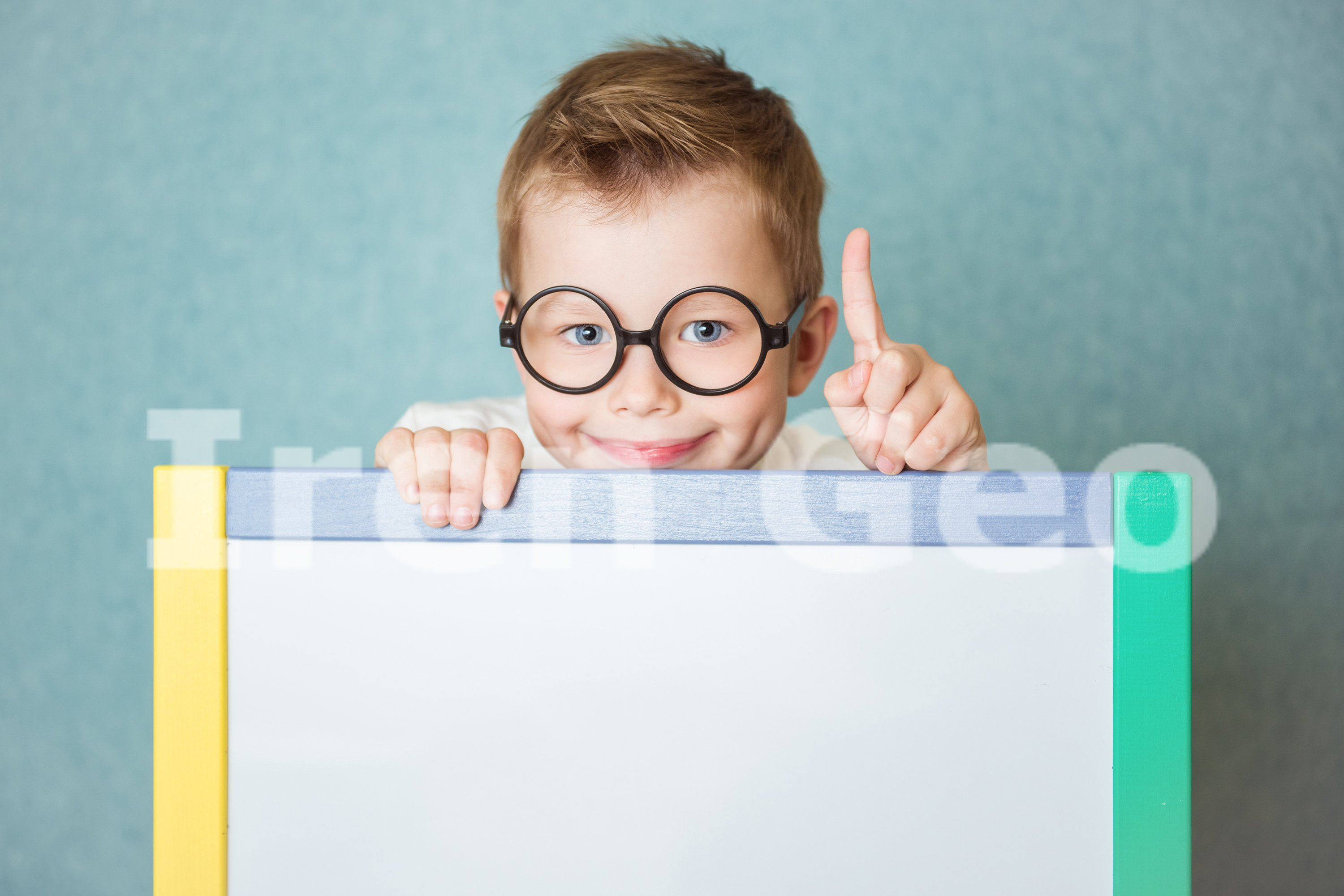 Young boy holding white blank board on blue background example image 1