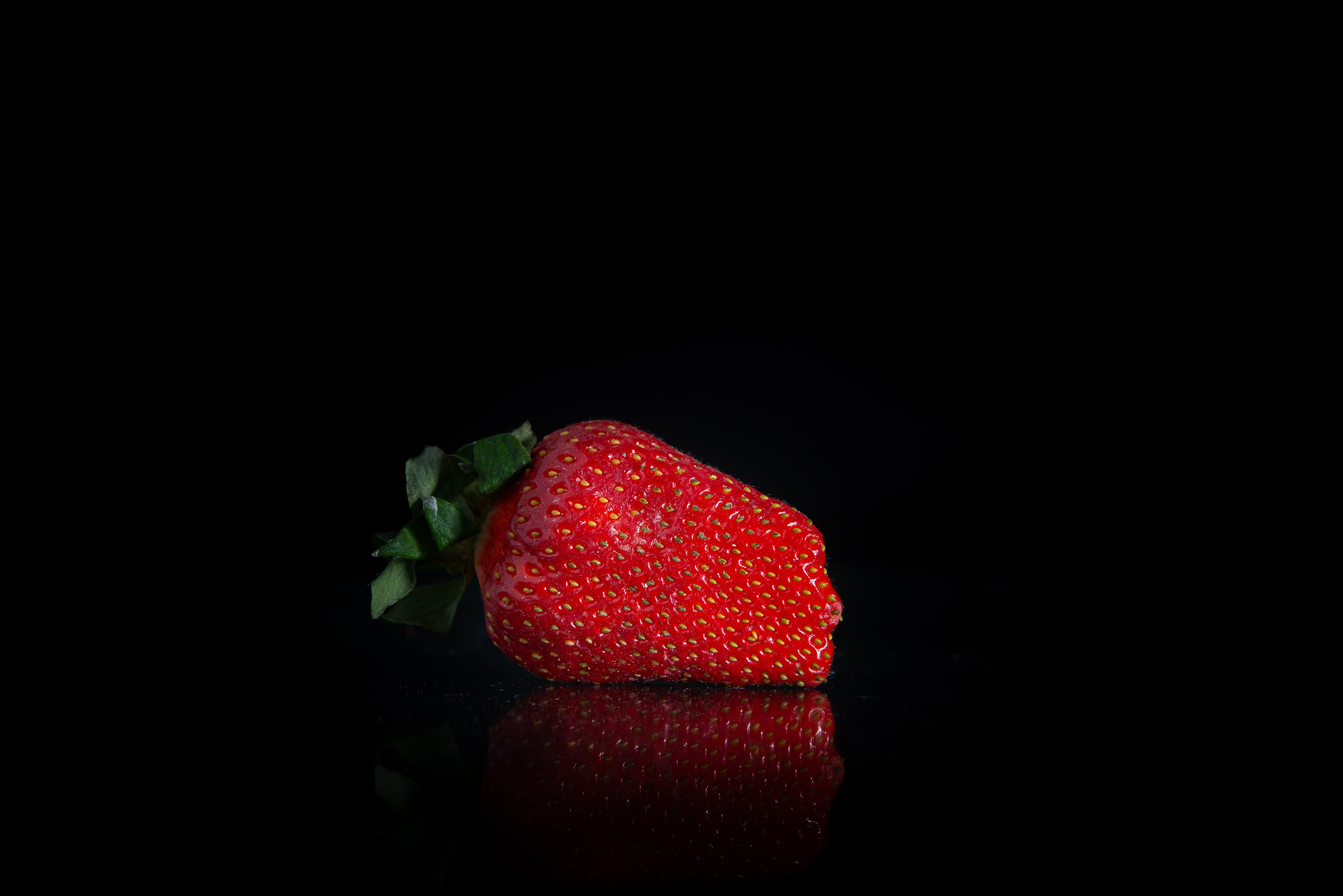 Giant fresh strawberries on a black background example image 1