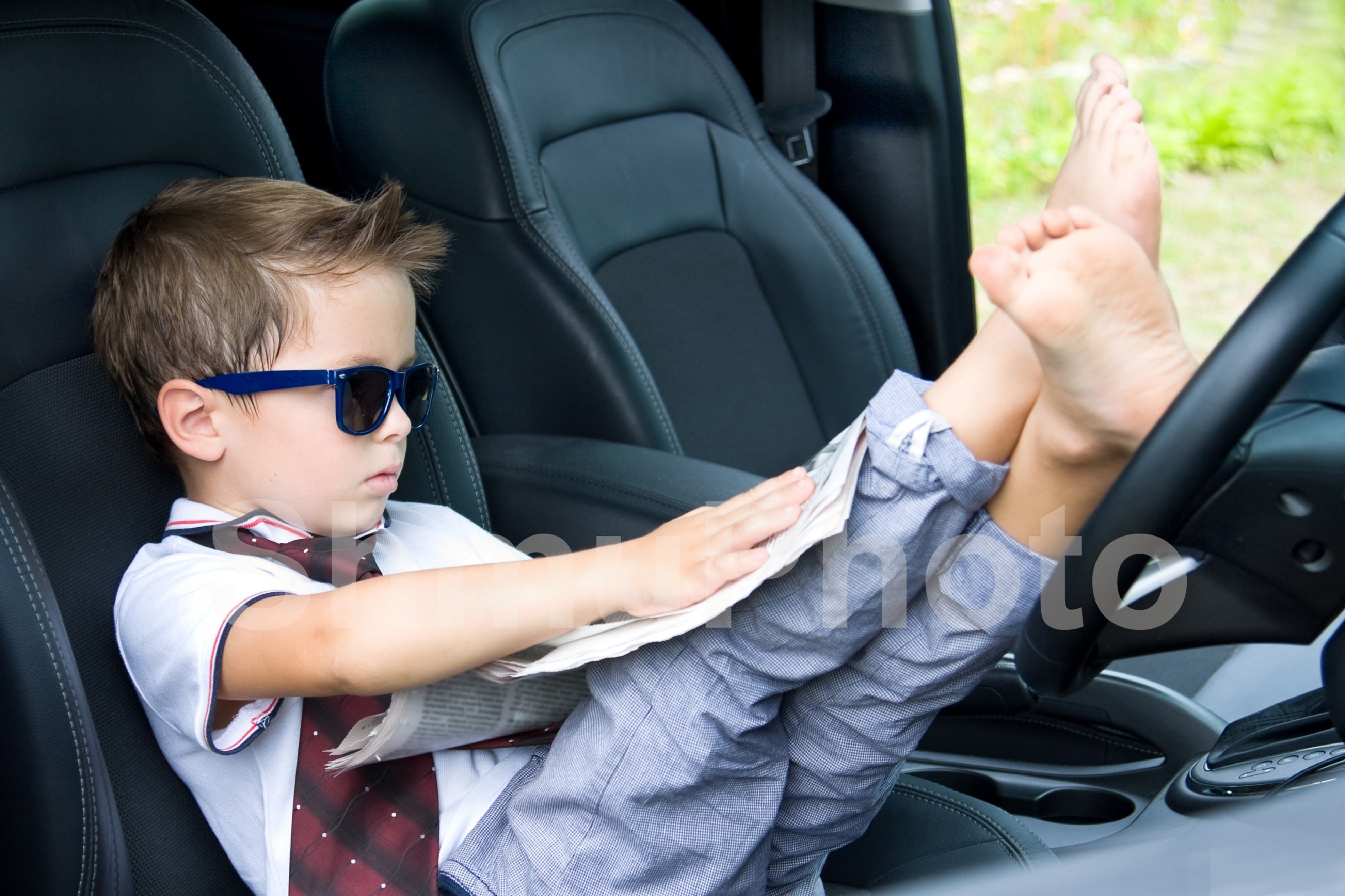 Cute driver. Smilng boy in sunglases in car example image 1