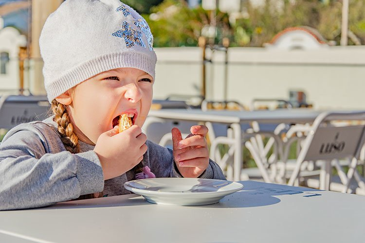 Hungry little girl eating cake in cafe outside example image 1