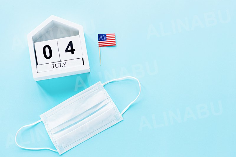 July 4th. USA flag and medical mask on blue background example image 1