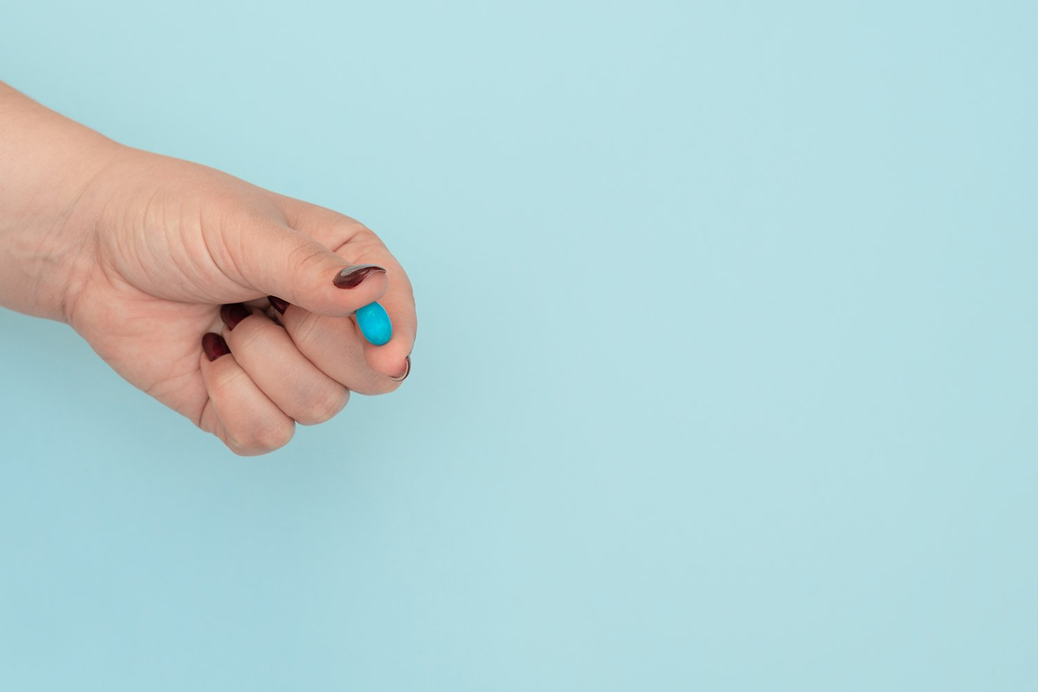 Blue pill on female hand on blue background example image 1