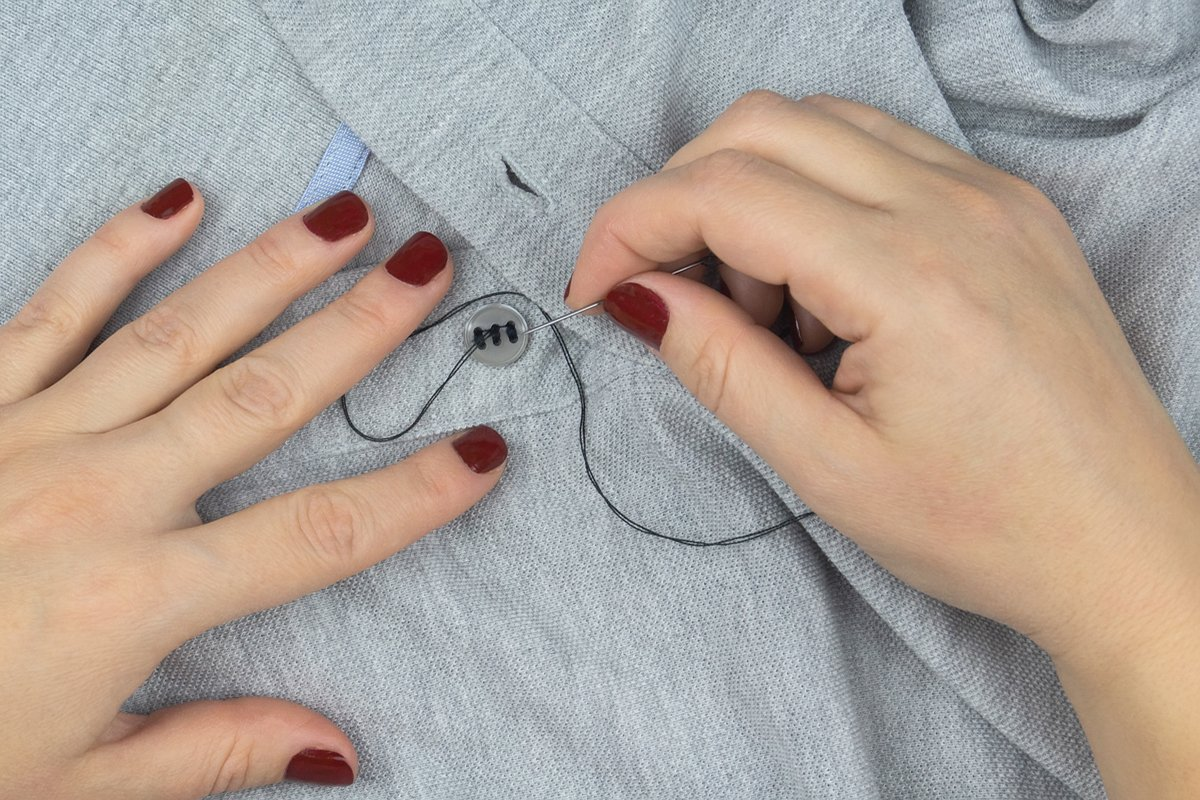 a girl with a needle in her hands sews a button to a shirt example image 1