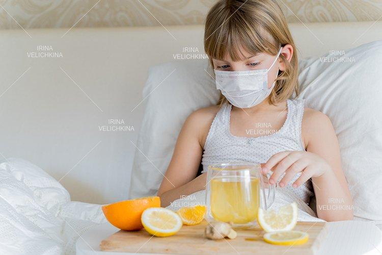 Sick girl in bed. Face mask.Cup of tea, orange,lemon,ginger example image 1
