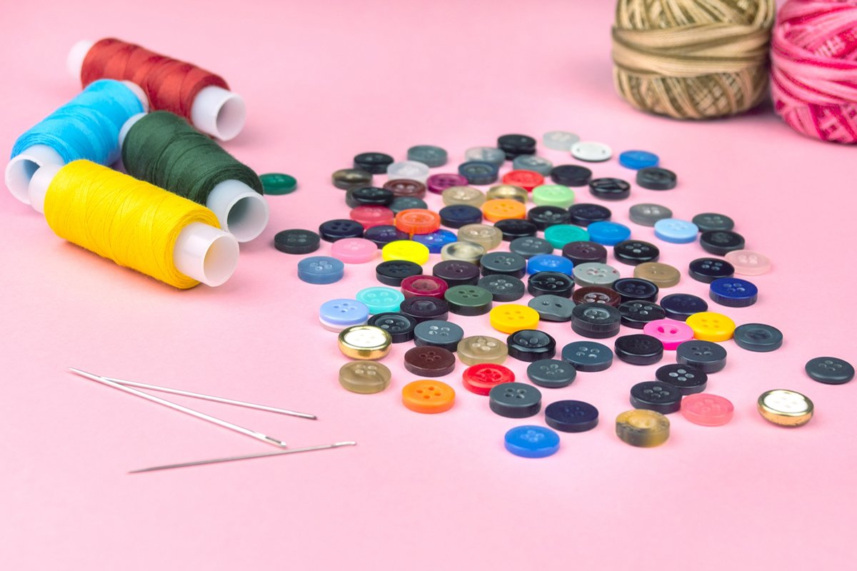 Multicolored threads and buttons on a pink background. example image 1