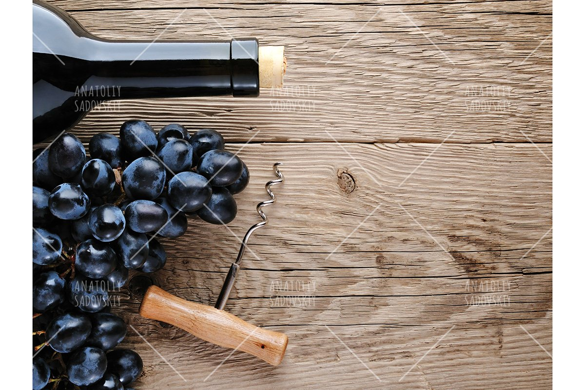 Bottle of wine, corkscrew and grape on wooden background example image 1