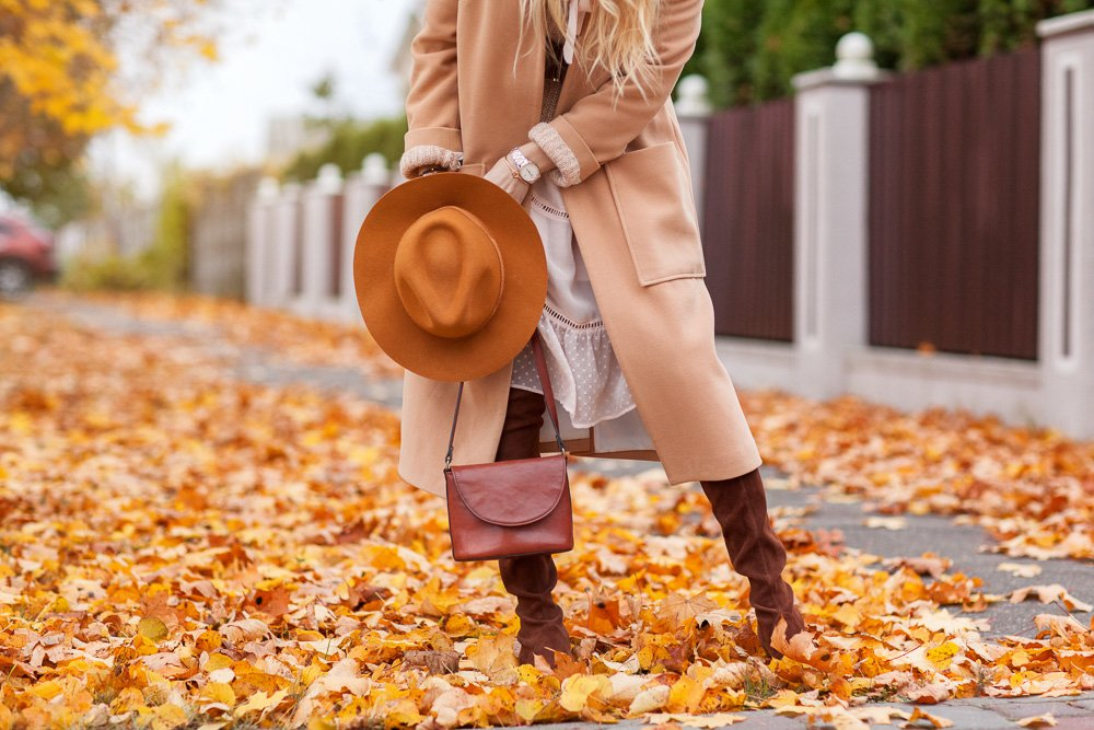 Girl walks through the autumn park in a coat and hat example image 1