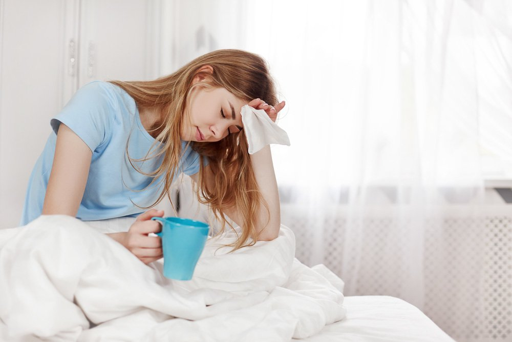 A sick girl with a headache is sitting under a blanket example image 1
