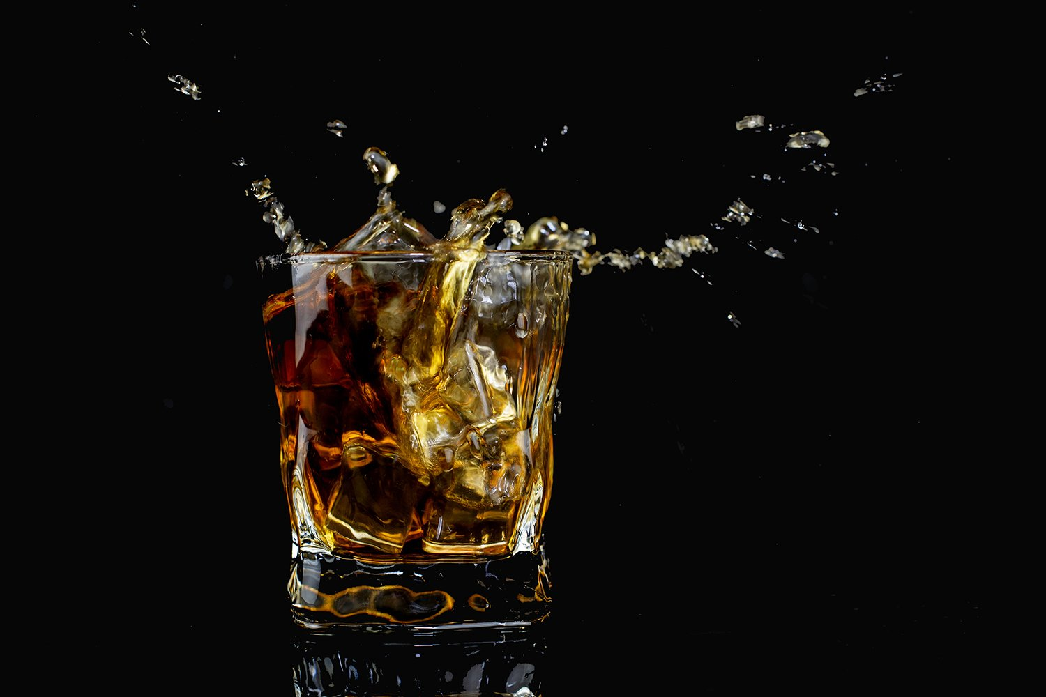 splash alcohol drink whiskey with ice with drops in a glass example image 1