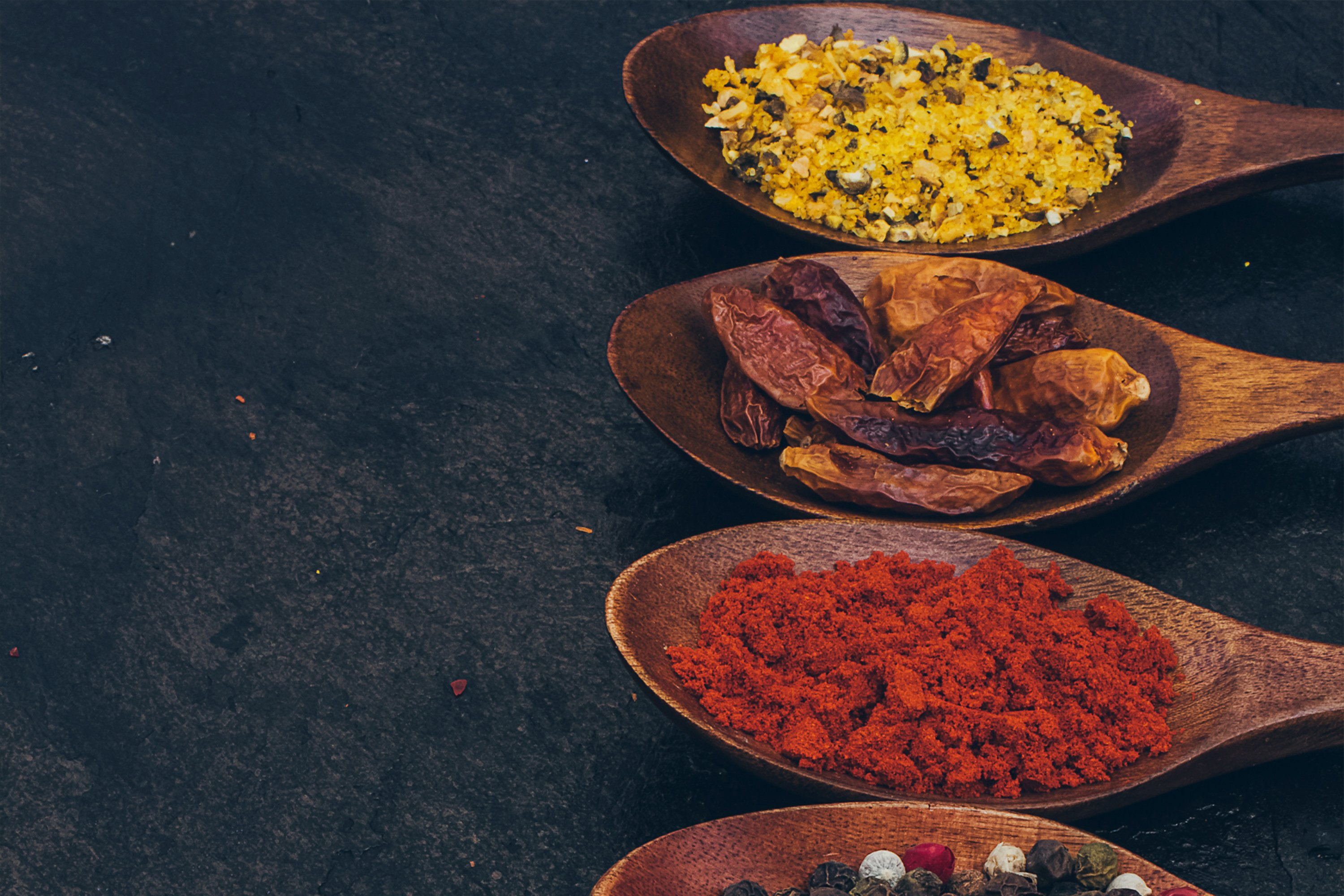 Colorful various spices in wooden spoons on old dark example image 1