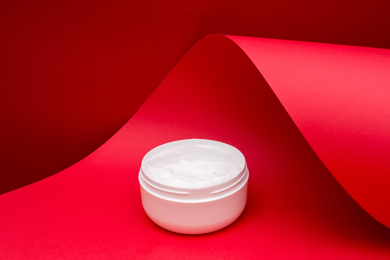 jar of beauty cream on red wave paper background example image 1