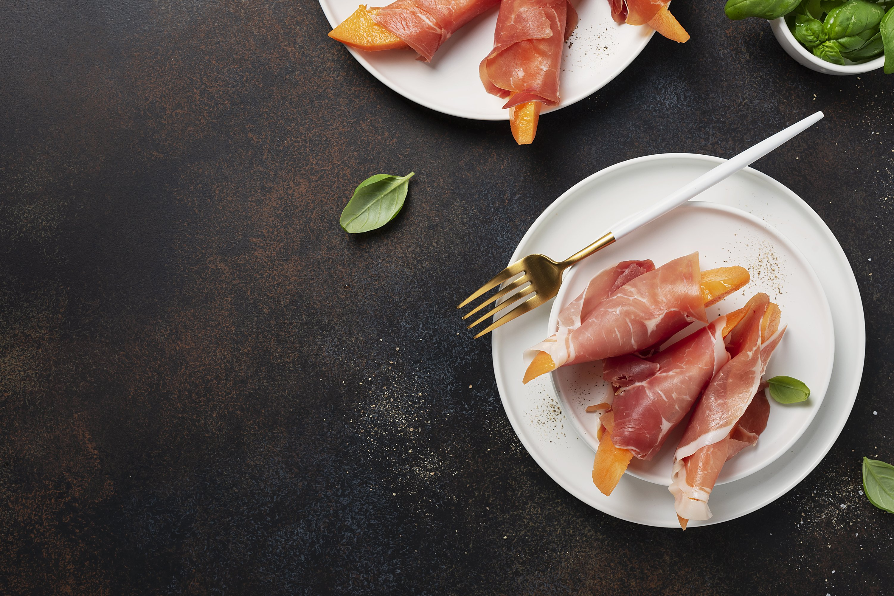 Summer appetizer with sweet melon and ham on dark background example image 1
