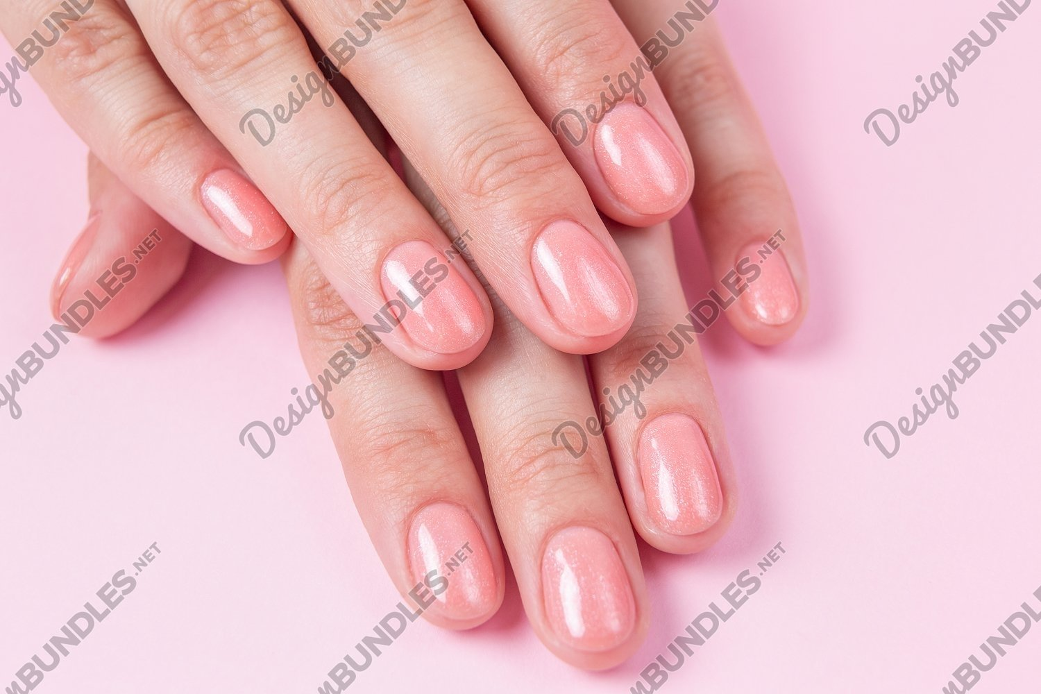 Nude nails covered with gel polish on a pink background example image 1