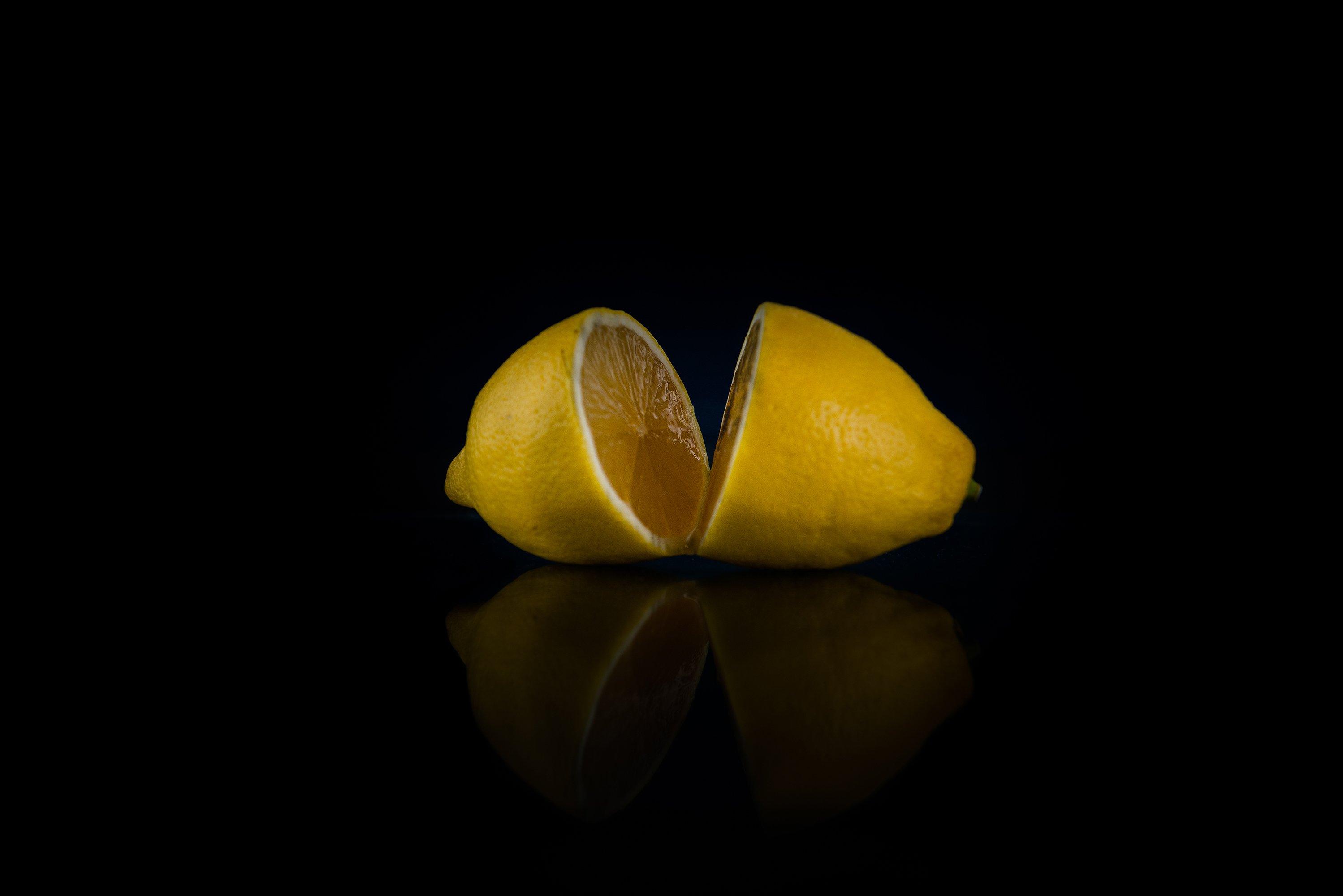two halves of whole lemon on a black background example image 1