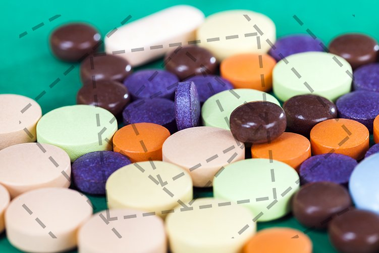 Multi-colored pills on a green background example image 1