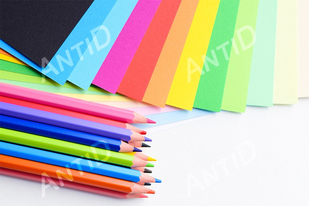 Colored pencils and colored paper on a white background example image 1