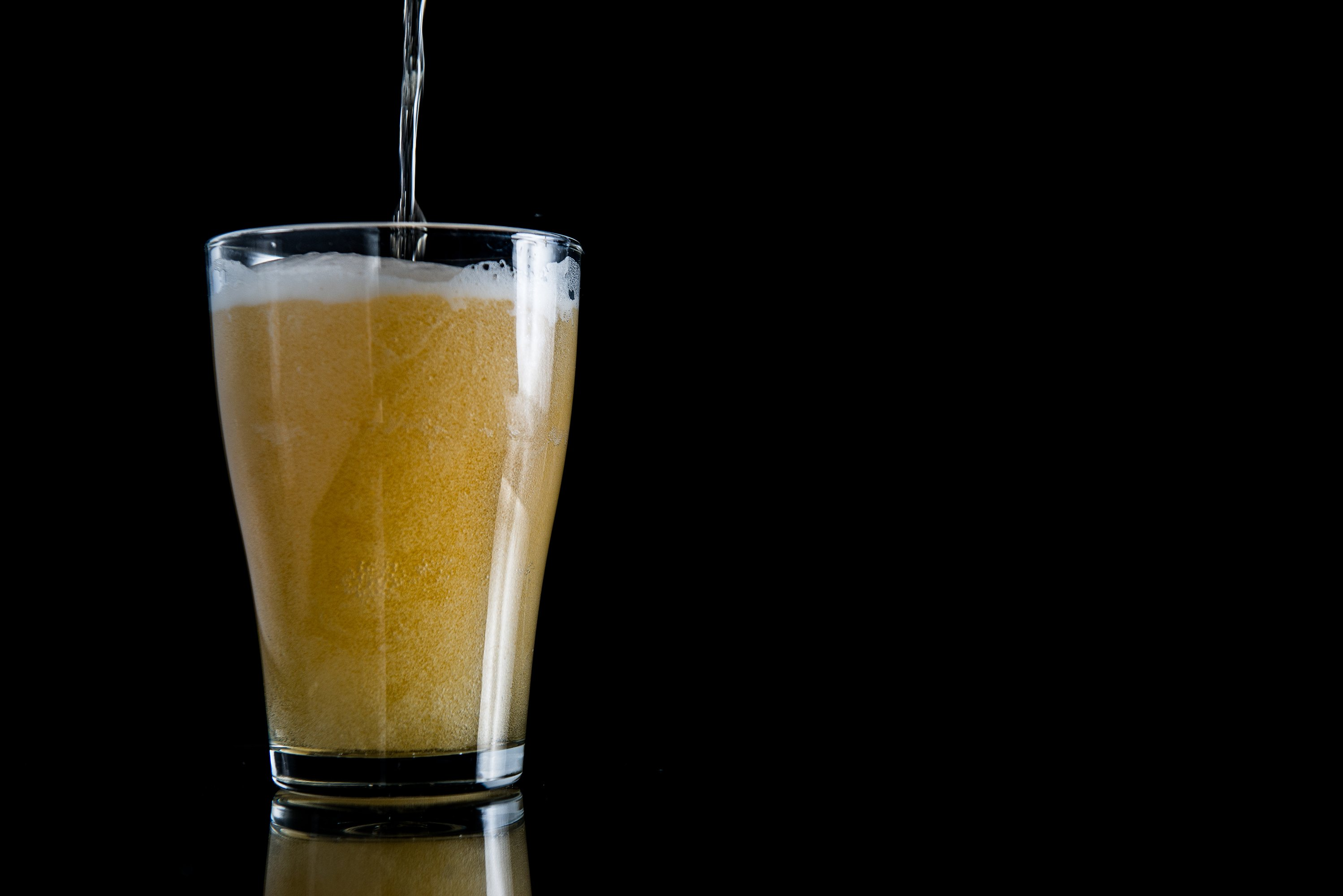 foam beer poured into a glass on a black background example image 1
