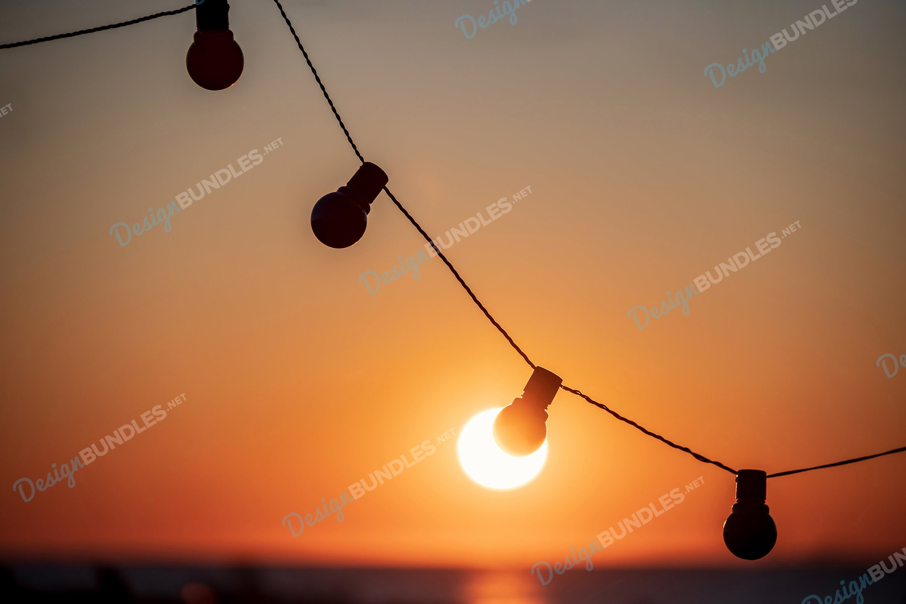 Stock Photo - Silhouette of incandescent lamps at sunset example image 1
