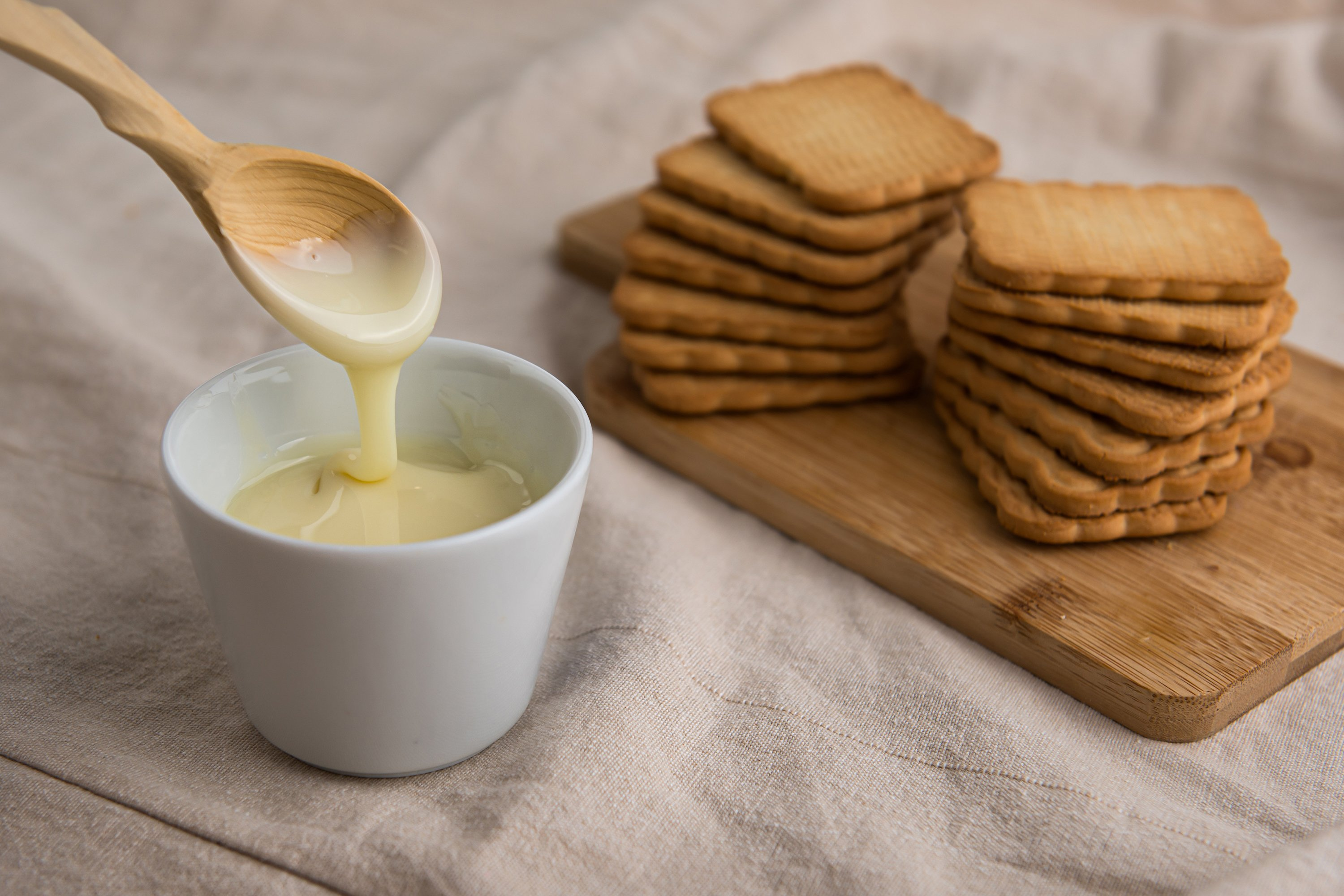 bowl with condensed milk with wooden spoon example image 1