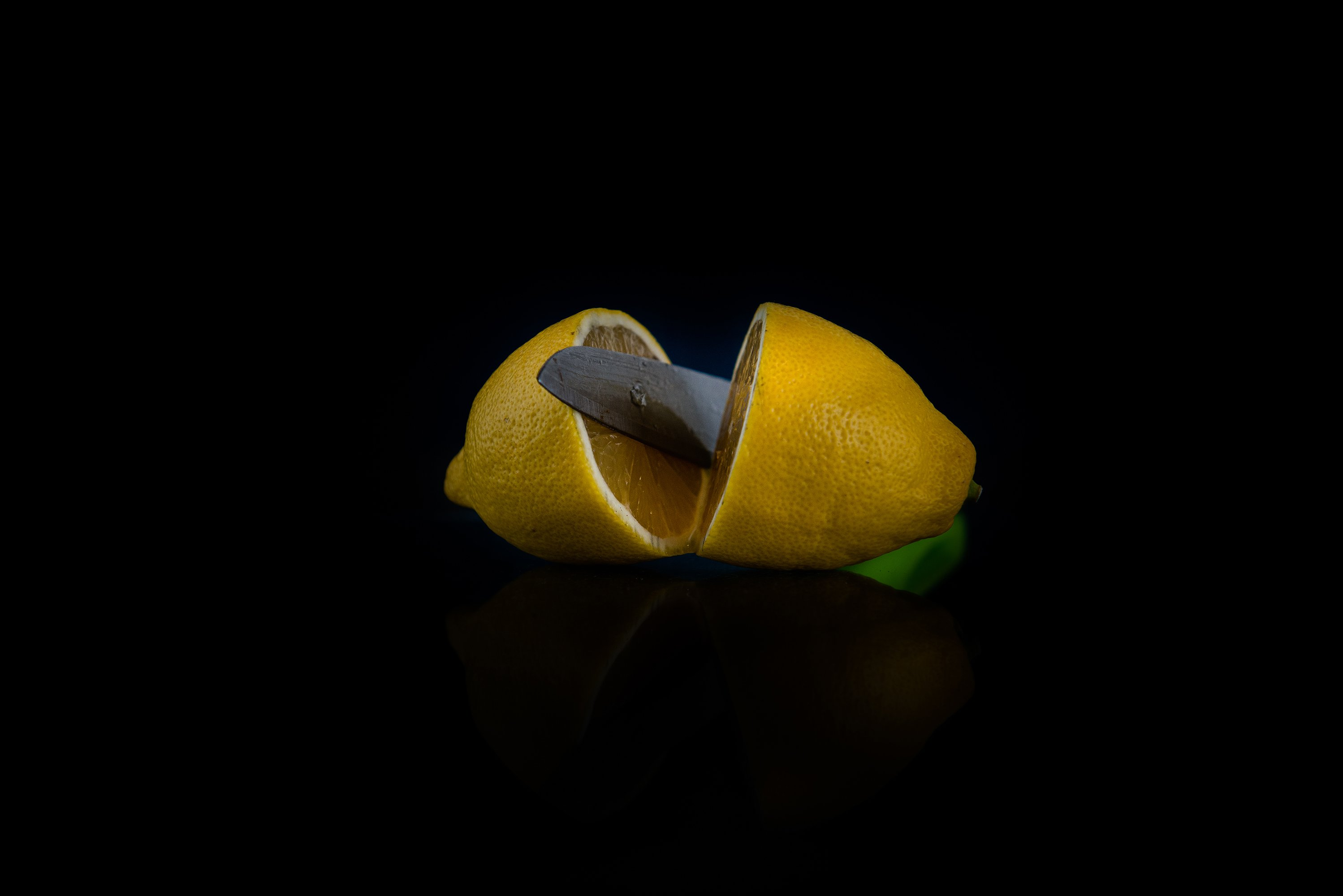 two halves of lemon cut with a knife on a black background example image 1