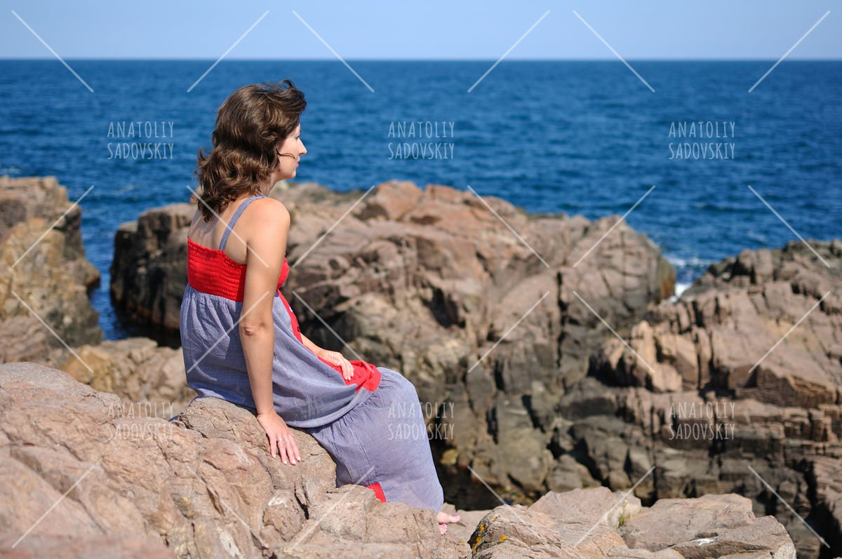 Woman sitting on rock near sea example image 1