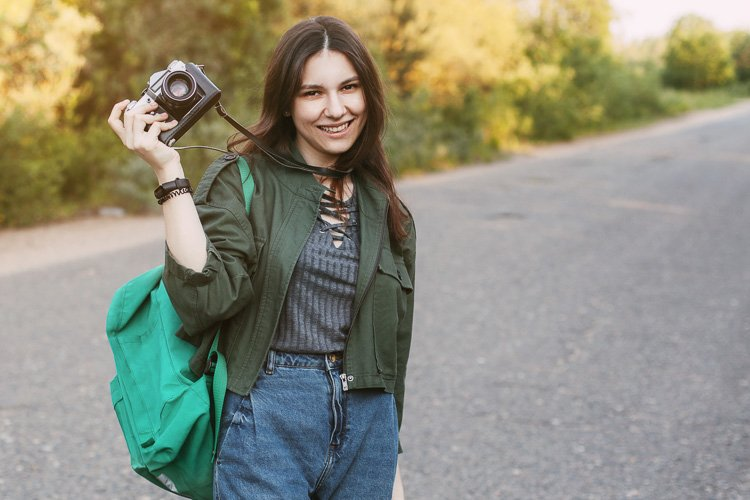 Cute brunette looks at the camera lens. A girl photographs n example image 1