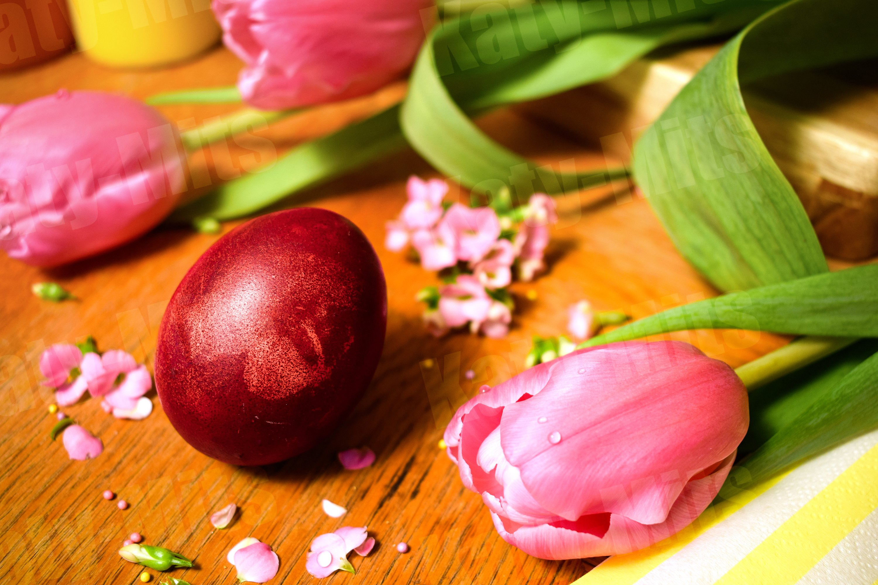 Easter eggs on a wooden table with pink flowers and petals. example image 1