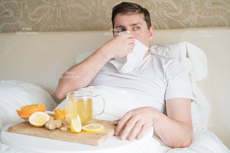 Sick man in bed. Cup of flu drugs. Tea, orange,lemon,ginger example image 1