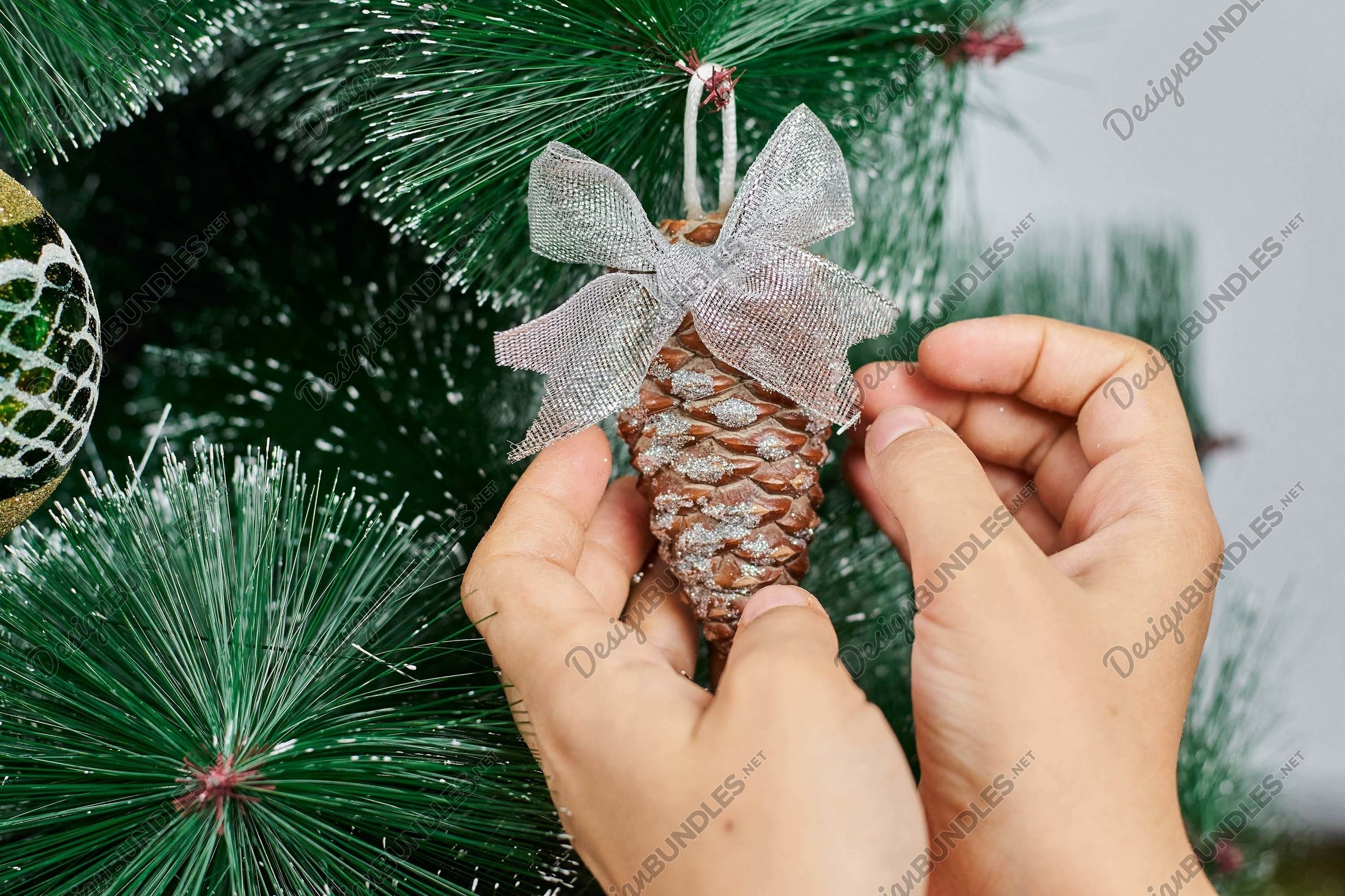 Stock Photo - Hands Of Woman Decorating Christmas Tree example image 1