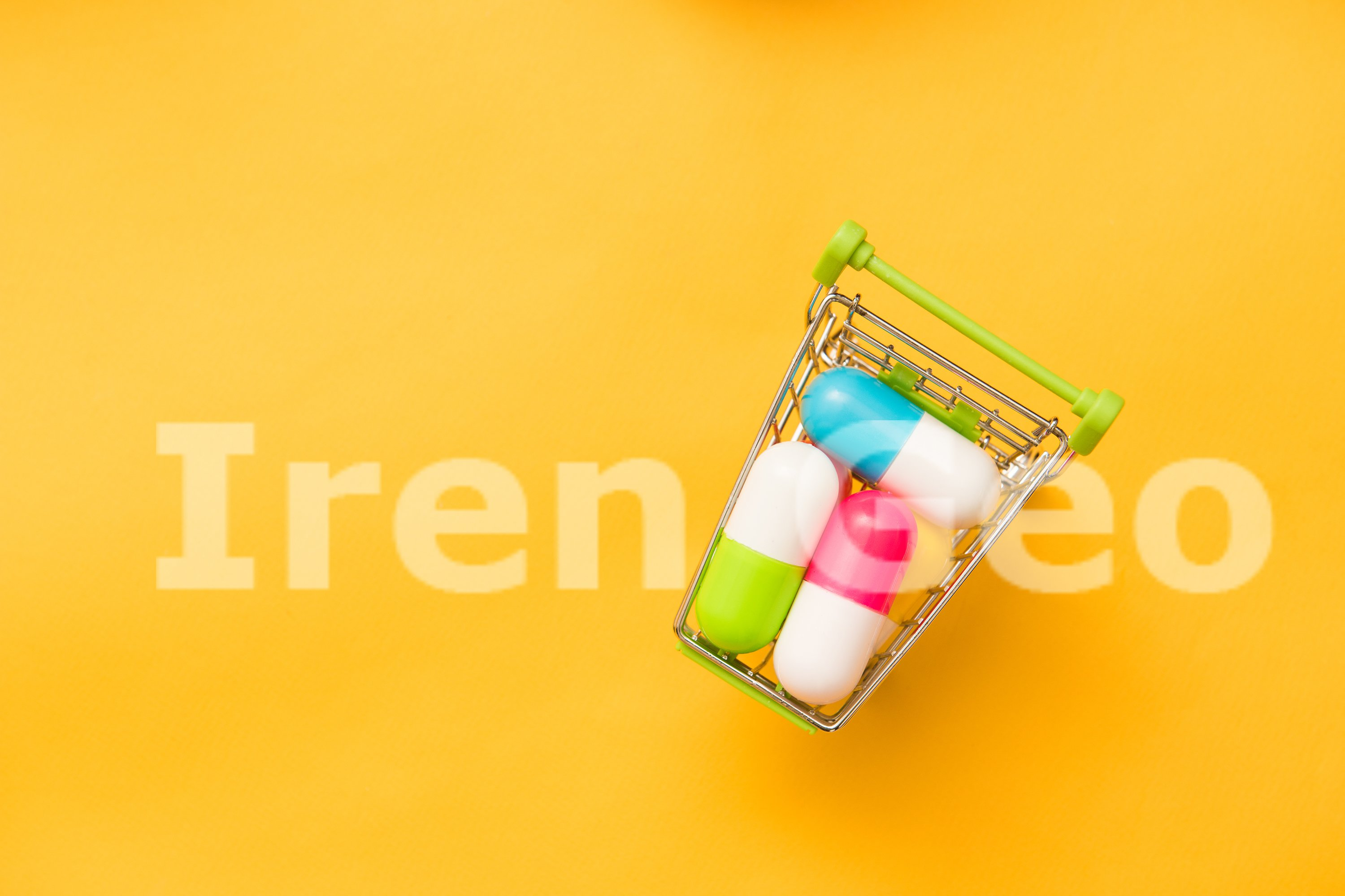 Small shopping cart full of pills on yellow background example image 1