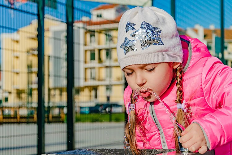 A pre-school girl drinks from a drinking fountain in a park. example image 1