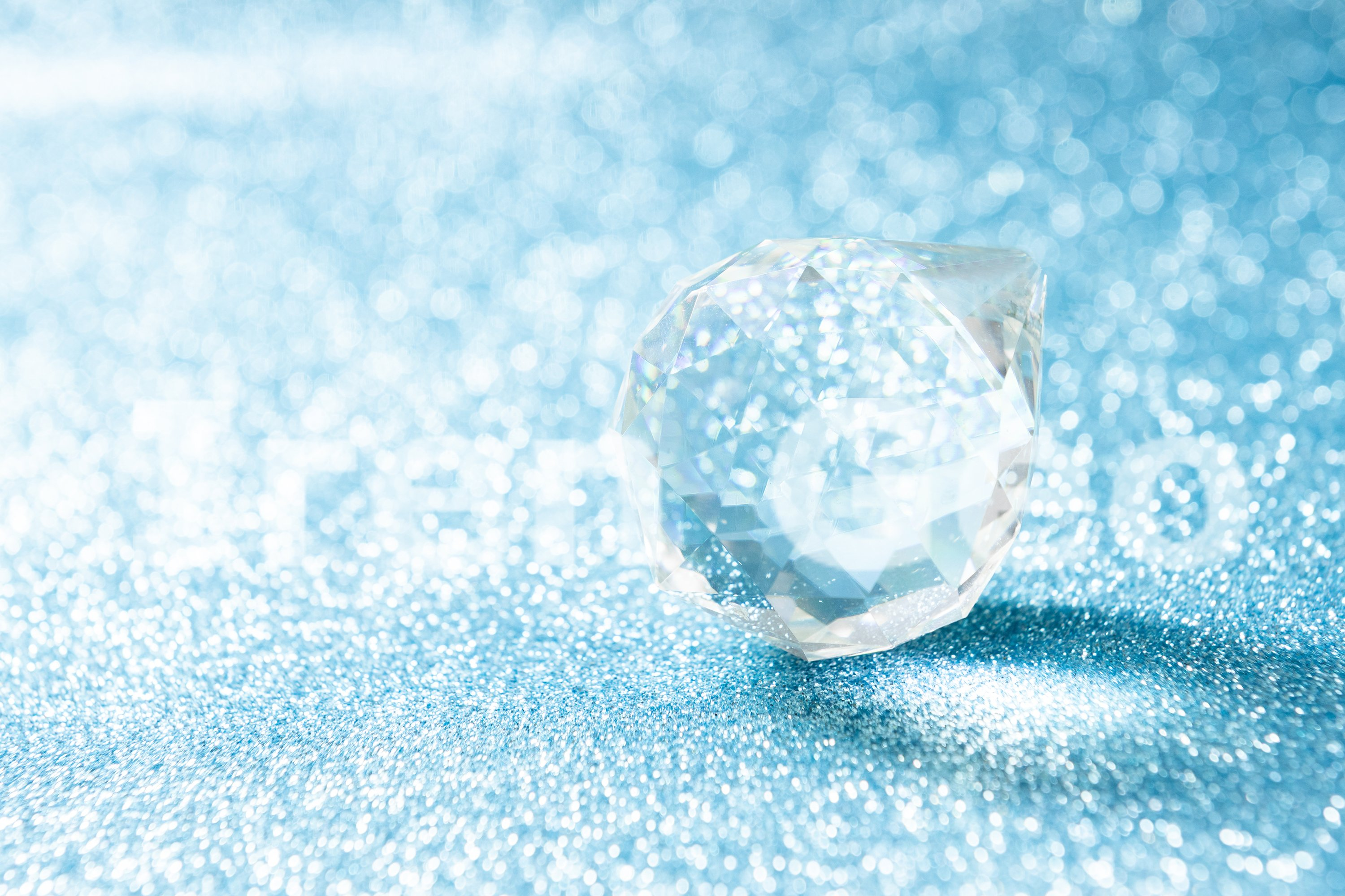 Transparent crystal in the shape of a ball on a bright blue example image 1
