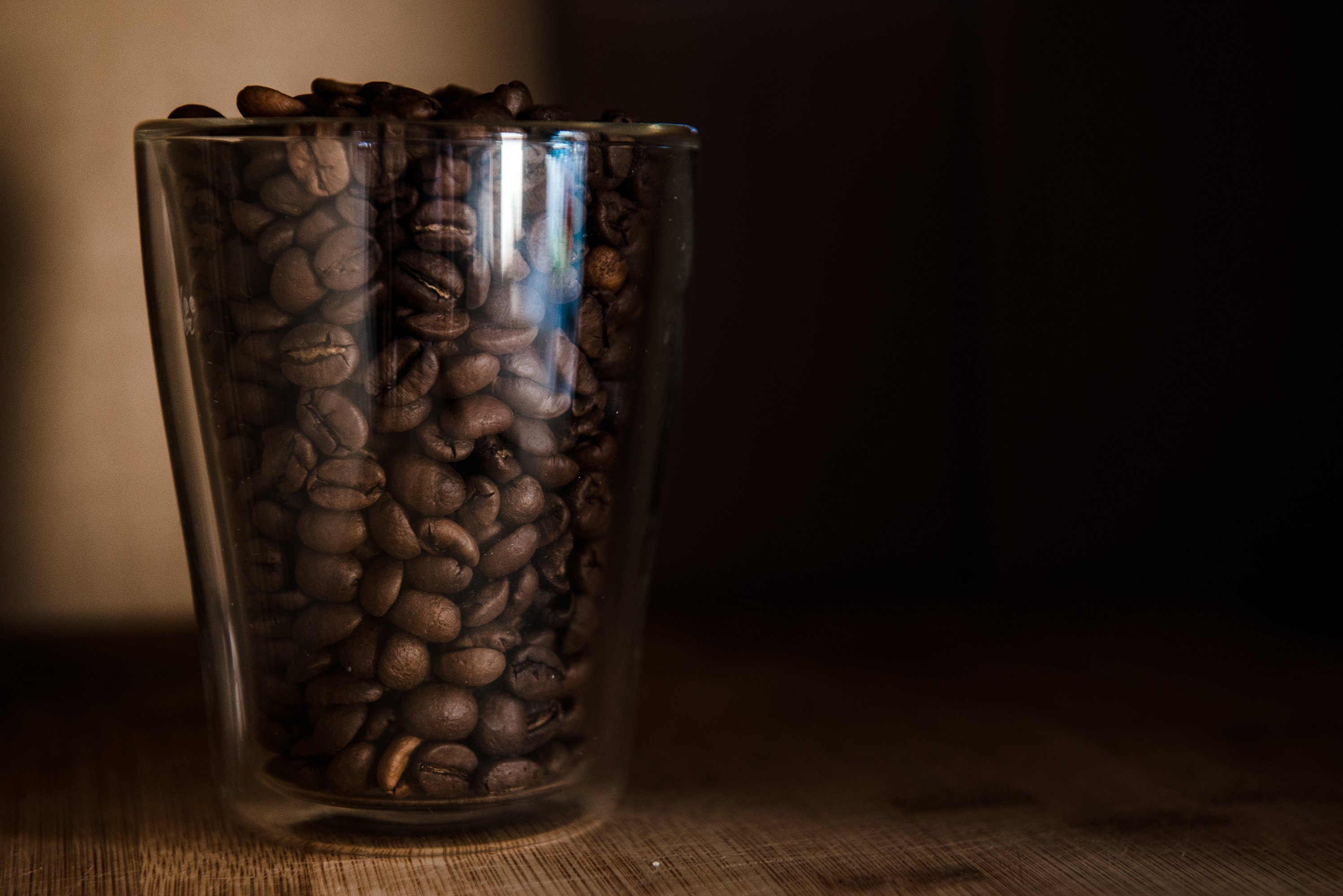 Coffee beans in glass cup on black background example image 1