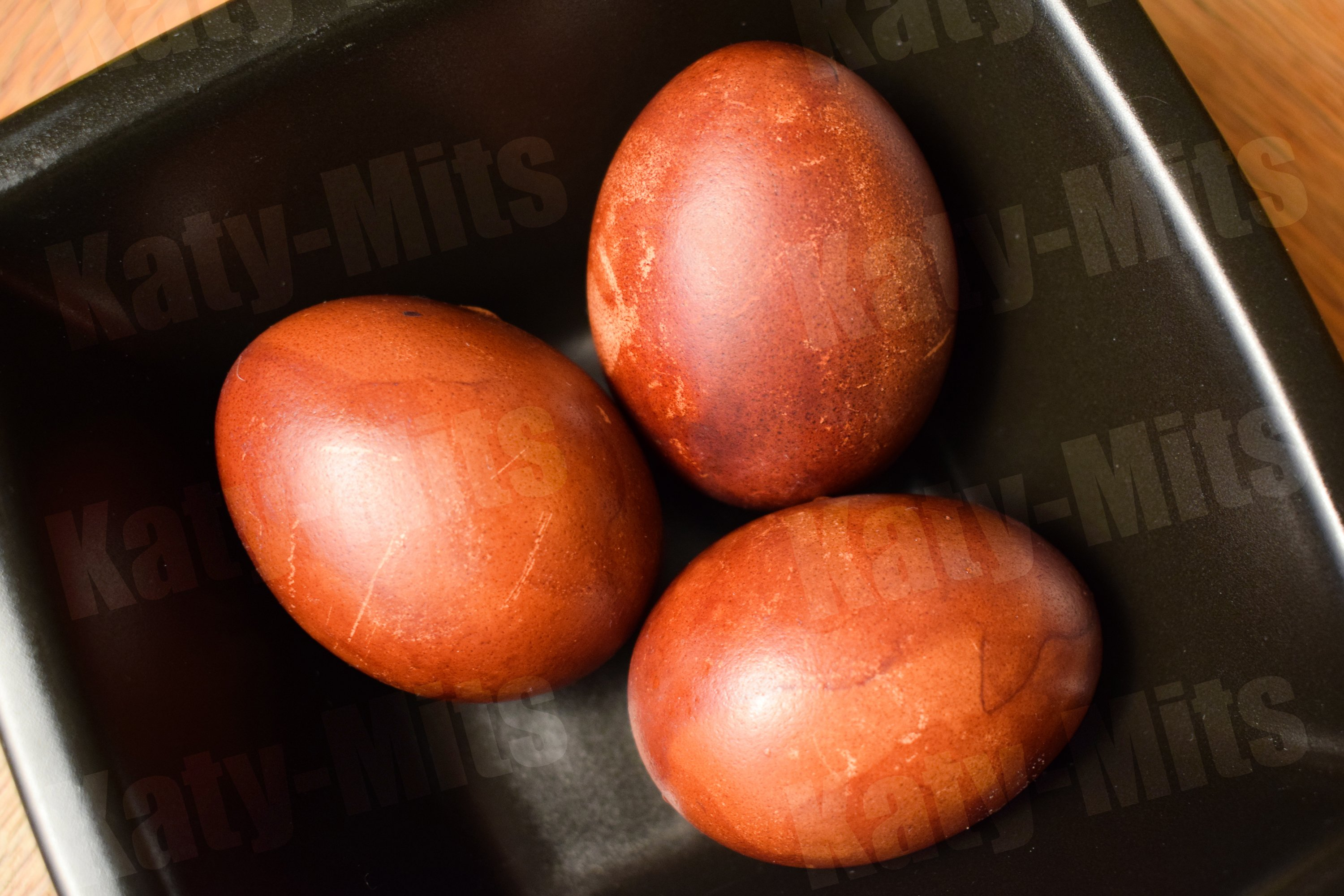 3 naturally colored Easter eggs in black bowl on wooden tabl example image 1